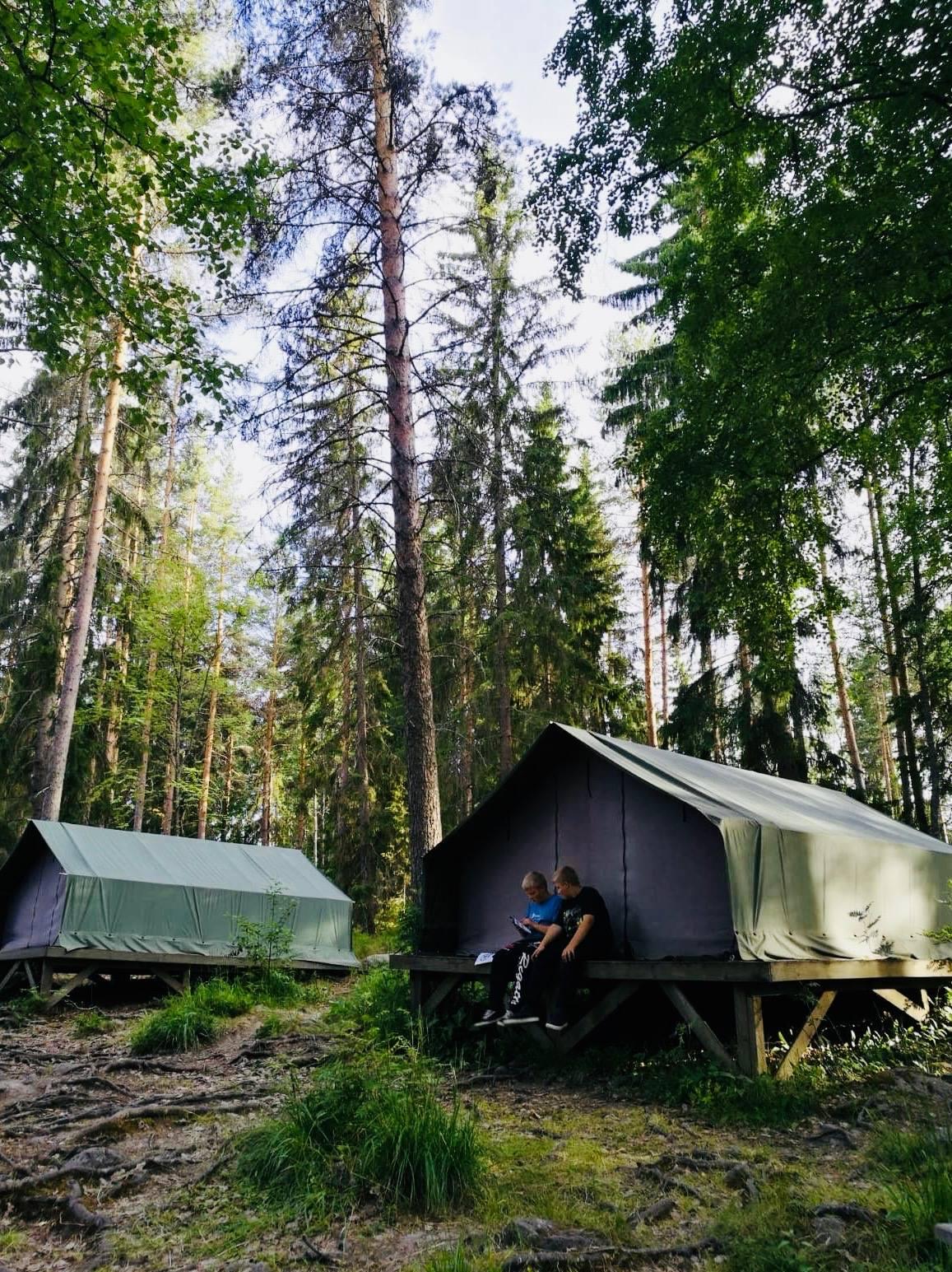 Telttakylässä kaksi leiriläistä istumassa teltan edessä