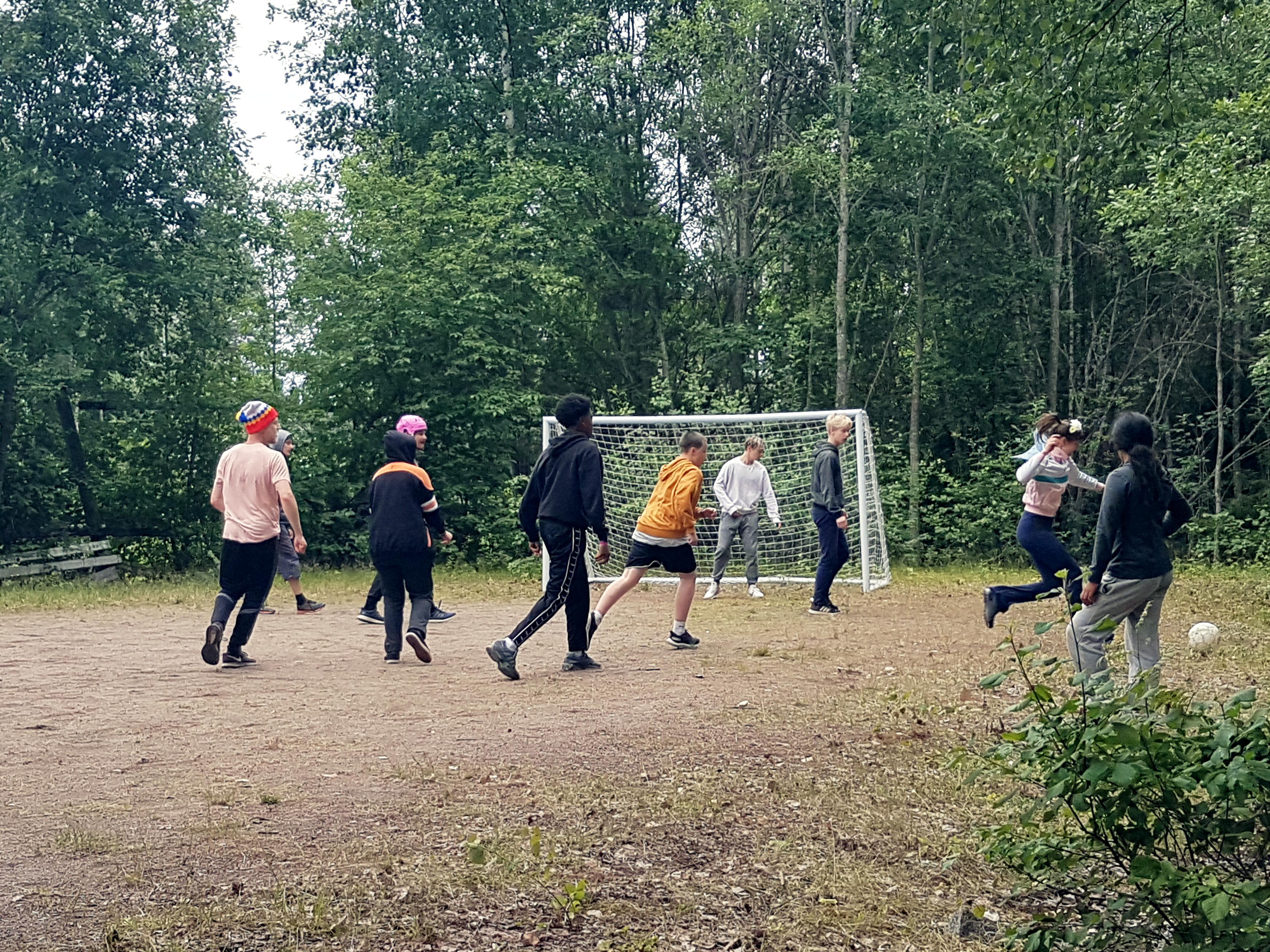 Alakentällä jalkapallomaalit, nuoria pelaamassa jalkapalloa