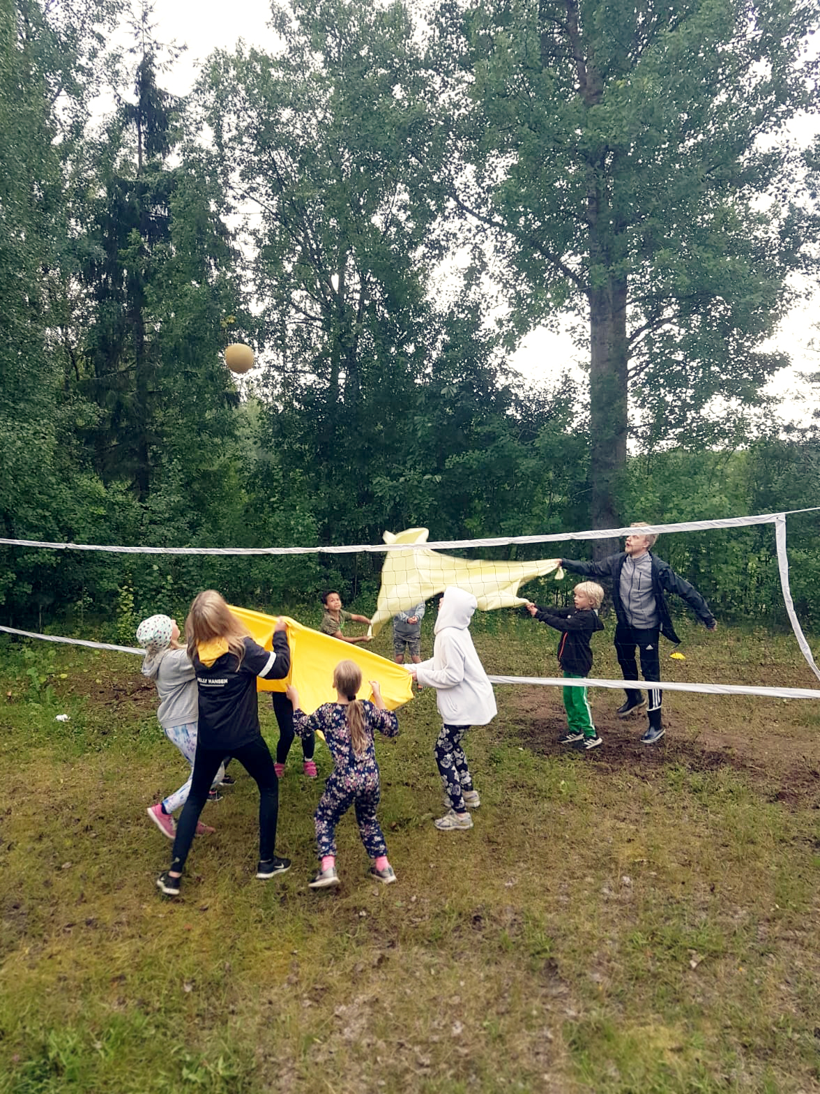 Yläkentän lentopallo- ja sulkapalloverkot ja lapsia pelaamassa lakanapallo-peliä