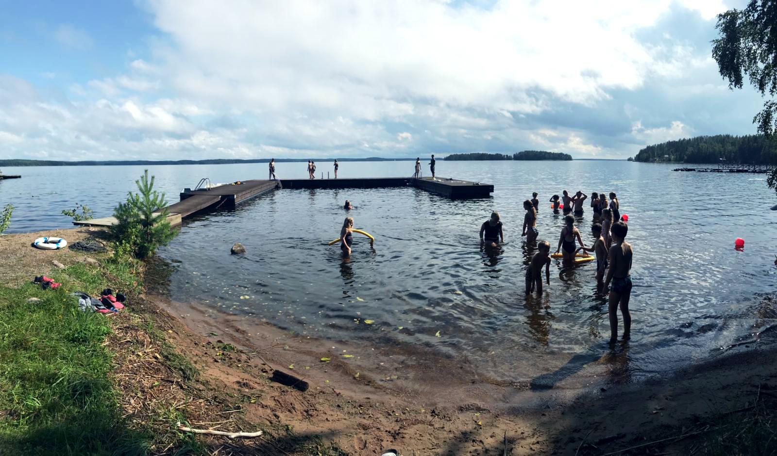 Leirikeskuksen uimaranta ja lapsia uimassa